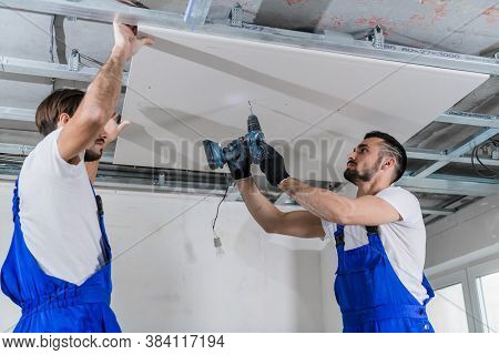 A Team Of Repairers Are Repairing The Ceiling In An Apartment. They Are Wearing Blue Work Clothes