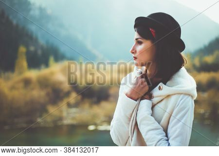A Young Woman In A White Coat Walking In Nature, Looks Away. Take Cover From The Autumn Cold. Toned