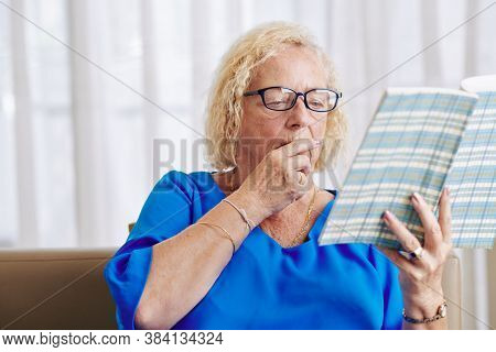 Aged Woman In Glasses Sitting On Sofa In Living Room And Reading Captivating Book