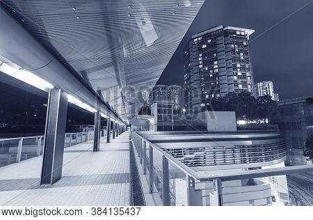 Modern Pedestrian Walkway In Midtown Of Hong Kong City At Night