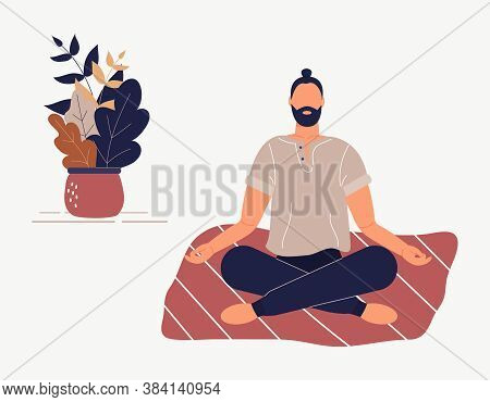 Hipster Man Sitting With His Legs Crossed On Floor And Meditating. Young Guy In Yoga Posture Doing M