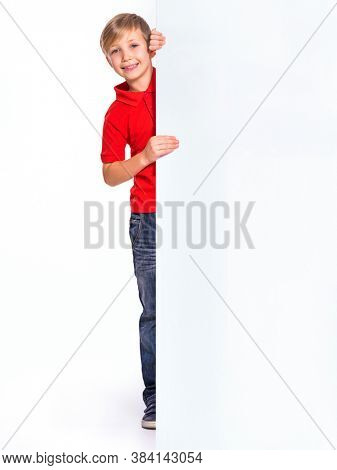 Happy kid look outs from the blank billboard. Portrait of a happy boy  with a white banner. Photo of a cheerful 8 years old kid looking at camera above an white paper banner, isolated on white