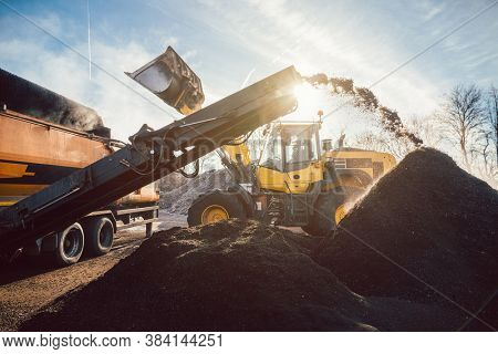 Heavy machinery moving earth and biomass in compost works or landfill