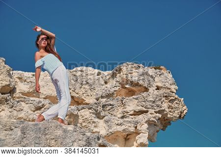 Woman Posing On Hill In Stylish Outfit. Blue Cloudless Sky.modeling For Professional Photoshoot. Cop