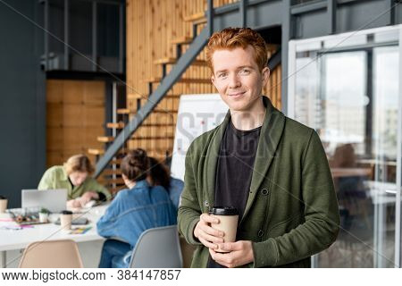 Young successful office manager in casualwear having drink in front of camera and looking at you against colleagues having meeting