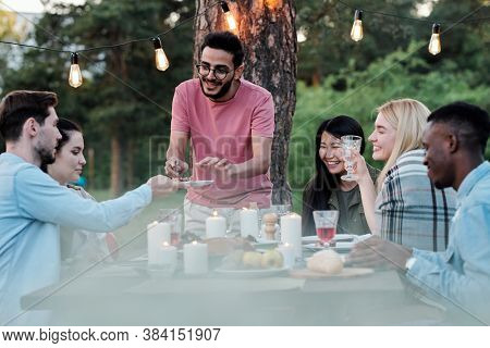Young smiling man of mixed-race ethnicity taking tasty food from plate held by Caucasian guy during gathering with friends under pine tree