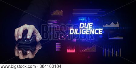 hand holding wireless peripheral with DUE DILIGENCE inscription, cyber business concept