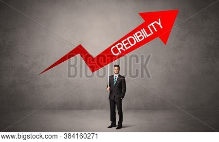 Young business person in casual holding road sign with CREDIBILITY inscription, business direction concept