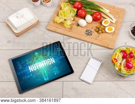 NUTRITION concept in tablet with fruits, top view