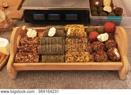 Balls And Rolls Of Soft Goat And Sheep Farm Cheese With Spices, Peppers And Spices On A Wooden Tray.
