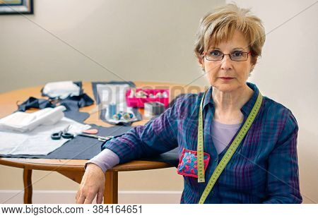 Senior Dressmaker Posing Looking At Camera With Table With Sewing Materials In The Background