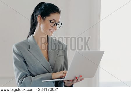 Self Confident Cheerful Woman Economist Analyzes Report About Company Income On Laptop Computer, Sha