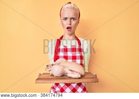 Young blonde woman wearing apron cooking chicken in shock face, looking skeptical and sarcastic, surprised with open mouth
