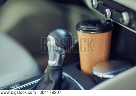 Close Up Shot Of A Paper Cup Of Coffee In The Cup Holder Between Seats Of Modern Car