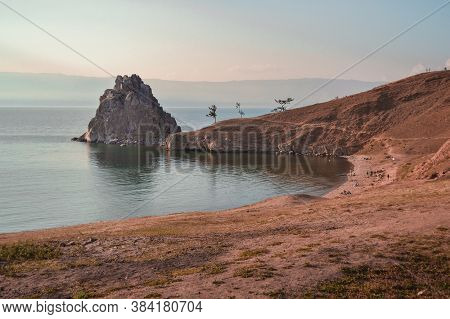 Cape Shamanka Rock In Clear Blue Lake Baikal Among The Grassy Steppes, Against The Background Of Mou