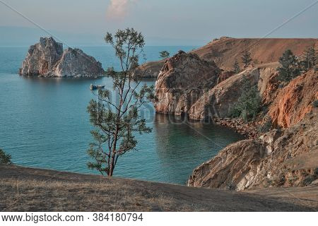 Cape Shamanka In Clear Blue Lake Baikal Among The Grassy Steppes With Coniferous Larch Trees, Red Ro