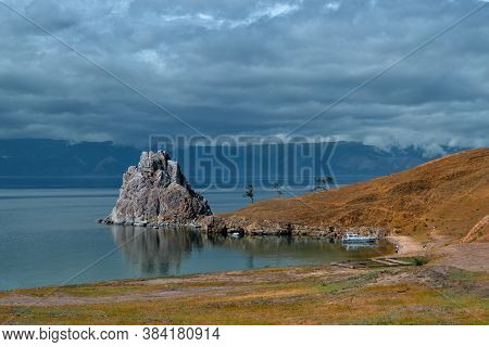 Cape Shamanka Rock In Blue Lake Baikal Among The Grassy Steppes, Against The Background Of Big Mount