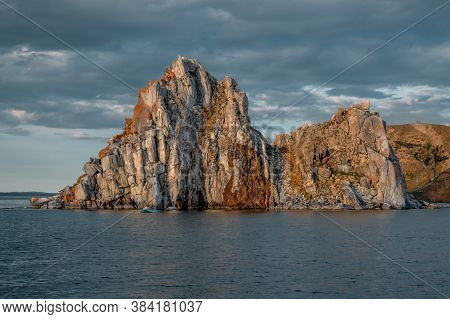 Cape Shamanka Rock In Blue Lake Baikal, Background Clouds, Sunset Light