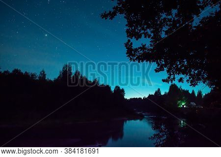 Night Sky In Nature. Tourist Have A Rest In His Camp Near The Forest At Night. Man Sitting Near Camp