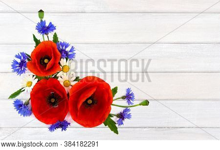 Red Poppies, Cornflowers And Chamomile On Background Of White Painted Wooden Planks With Space For T
