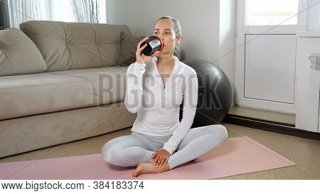 Attractive Young Sportswoman In Comfortable Tracksuit Drinks Water Resting After Intense Training On