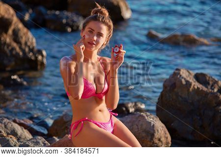 Lady Applying Sunblock On Body Holding Red Clock. Sun Protection. Tan And Relax. Woman In Pink Bikin