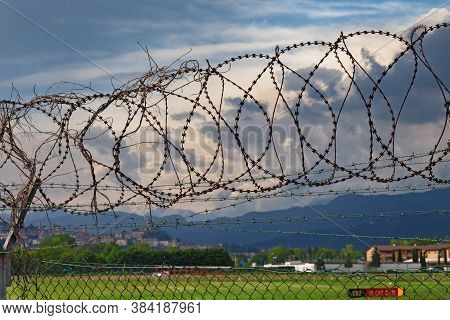 Bergamo, Italy - May 21, 2019: Barbed Wire That Encloses The Territory Of The Orio Al Serio Internat