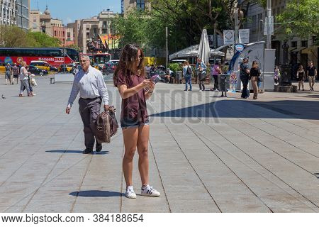 Barcelona, Spain - May 15, 2017: Unknown Young Attractive Woman With Cellphone Standing On The Placa