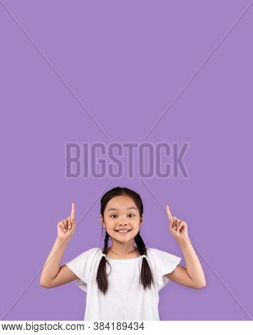 Look Up. Adorable Asian Kid Girl Pointing Fingers Upward At Copy Space Standing Over Purple Studio B