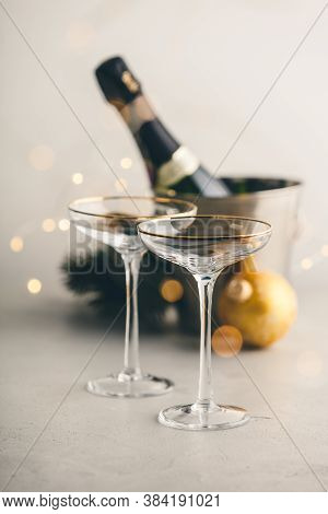 Champagne Bottle In Bucket With Ice, Glasses And Christmas Decorations