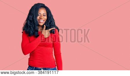 Beautiful african american woman wearing casual clothes cheerful with a smile of face pointing with hand and finger up to the side with happy and natural expression on face