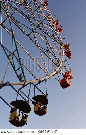 A Part Of White Ferris Wheel With Colorful Cabins Against The Backgroud Of The Blue Sky With Clouds.