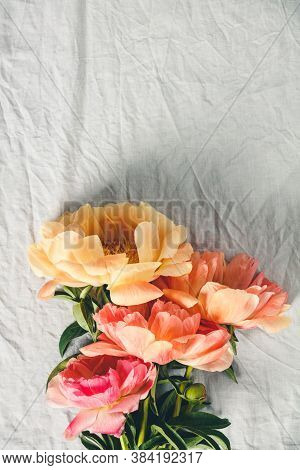 Flat-lay Of Beautiful Peony Flowers Over Grey Linen Table Cloth Background, Top View, Copy Space