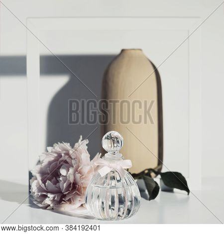 Pink Peopy Flower, Perfume Bottle, Vase And White Wooden Frame Against White Wall