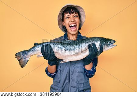 Beautiful brunettte fisher woman showing raw salmon celebrating crazy and amazed for success with open eyes screaming excited.