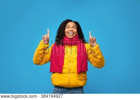 Look Up. Joyful Black Woman In Winter Jacket Pointing Fingers Upward Standing Over Blue Background.