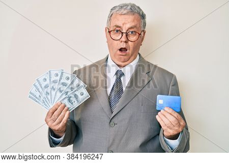 Senior grey-haired man wearing business suit holding credit car and dollars in shock face, looking skeptical and sarcastic, surprised with open mouth
