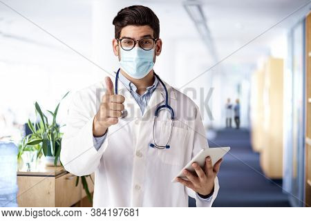Shot Of Male Doctor Wearing Face Mask While Standing On The Hospital's Foyer And Giving Thumbs Up.