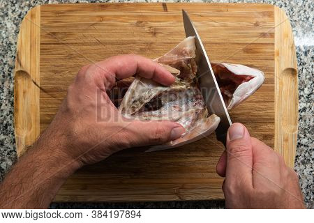 Caucasian Male Hand Holding A Kitchen Knife Preparing To Cut And Gut A Market Frozen Raw Sea Bream F