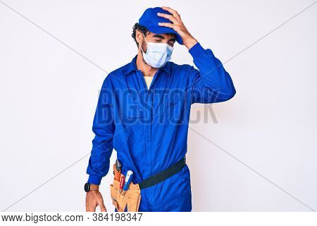 Handsome young man with curly hair and bear wearing handyman uniform and covid-19 safety mask surprised with hand on head for mistake, remember error. forgot, bad memory concept.