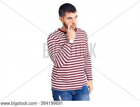 Young handsome man wearing striped sweater pointing to the eye watching you gesture, suspicious expression