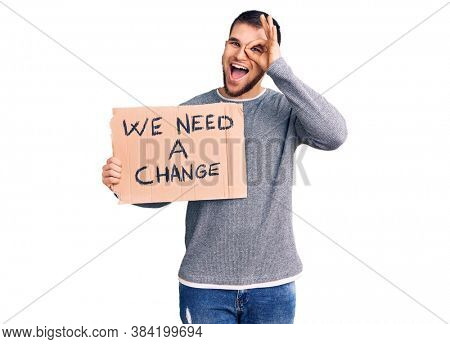 Young handsome man holding we need a change banner smiling happy doing ok sign with hand on eye looking through fingers