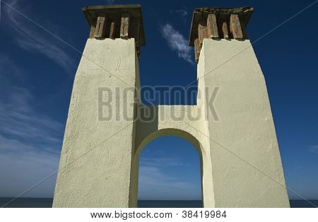 an arch joint and hold two smokestack, the sea at the botton, Huelva, Spain poster