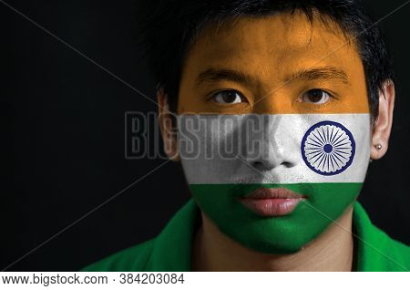 Portrait Of A Man With The Flag Of The India Painted On His Face On Black Background. Tricolor Of In