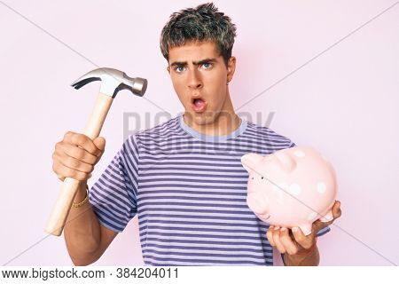 Young handsome man holding piggy bank and hammer in shock face, looking skeptical and sarcastic, surprised with open mouth
