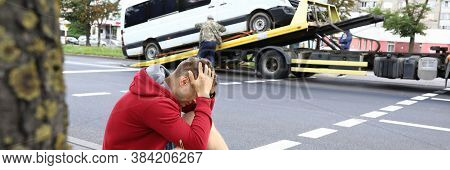 Man Sits On Side Of Road Holding His Head With His Hands Next To Wrecked Car After Car Accident. Tra