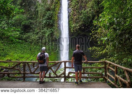 Two Tourists Looking At The La Fortuna Waterfall In Costa Rica. The Waterfall Is Located On The Aren