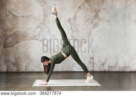 Young Strong Attractive Woman Wearing Sportswear, Working Out In Yoga Studio Near Wall Textured Back