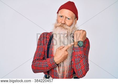 Old senior man with grey hair and long beard wearing hipster look with wool cap in hurry pointing to watch time, impatience, looking at the camera with relaxed expression