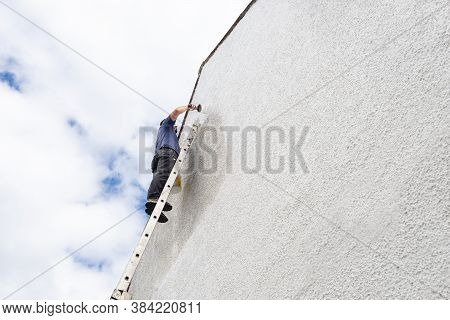 Hardworking Man High Up A Ladder Paints Side Of House A Fresh White Colour.